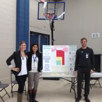 Students Pose next to Blood Pressure Screening poster